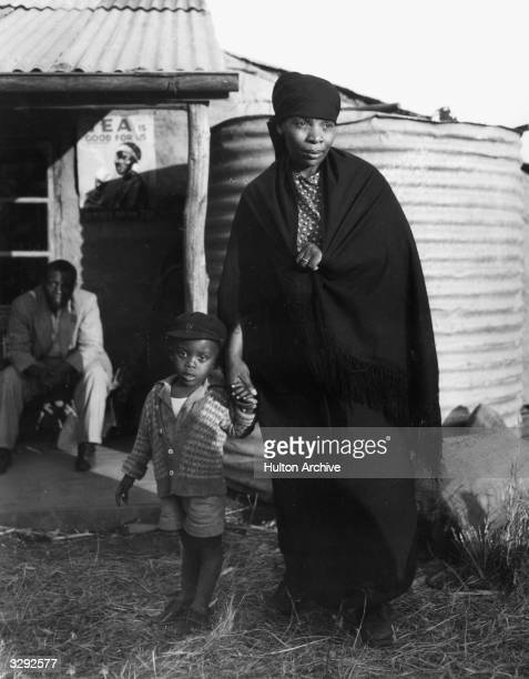 Albertina Temba and Tsepo Gugushe leave their corrugated metal shack in the London Films drama of racial tension 'Cry The Beloved Country' directed...