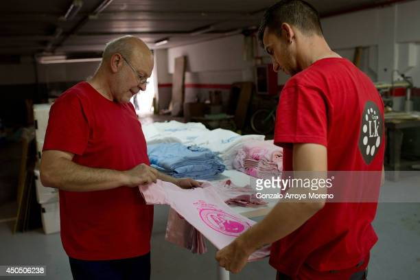 Alberto, 53 and his manager Alejo examinate a freshly baked t-shirt of Prince Felipe and Princess Letizia as future Spanish monarchs of Spain at LK...
