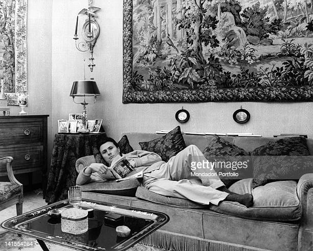 Alberto Arbasino Italian writer essayist and journalist reading while lying on a couch