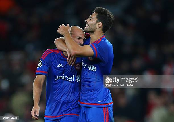 Alberto Botia and Esteban Cambiasso of Olympiacos celebrate the win after the UEFA Champions League match between Arsenal and Olympiacos at the...