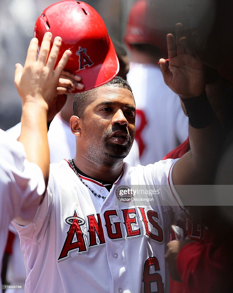 Alberto Callaspo #6 of the Los Angeles Angels of Anaheim celebrates with teammates in the dugout after scoring on a fielder's choice to third base by Chris Iannetta #17 (not in photo) during the MLB game against the Pittsburgh Pirates at Angel Stadium of Anaheim on June 23, 2013 in Anaheim, California. The Pirates defeated the Angels 10-9 in ten innings.