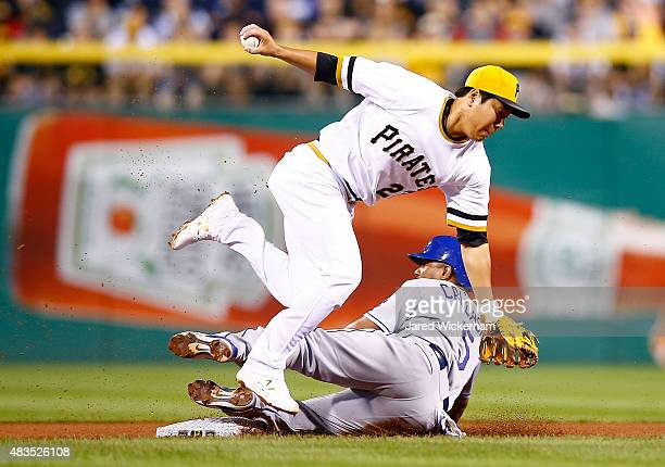 Alberto Callaspo of the Los Angeles Dodgers breaks up an attempted double play at second base by Jung Ho Kang of the Pittsburgh Pirates during the...