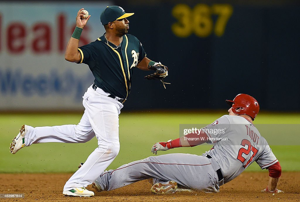 Alberto Callaspo #7 of the Oakland Athletics looks to complete the double-play over the top of Mike Trout #27 of the Los Angeles Angels of Anaheim in the top of the six inning at O.co Coliseum on August 22, 2014 in Oakland, California. Callaspo got his throw off in time to get Albert Pujols #5 of the Angels at first base.