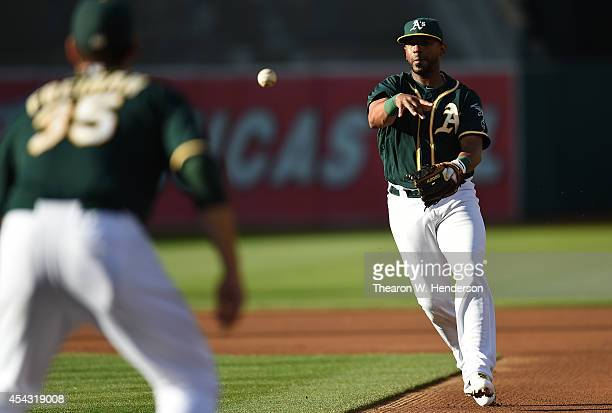 Alberto Callaspo of the Oakland Athletics throws out Collin Cowgill of the Los Angeles Angels of Anaheim in the top of the first inning at Oco...