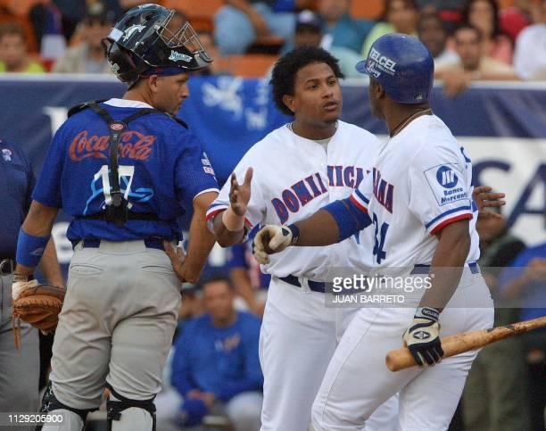 Alberto Castillo of the Dominican Republic Tigres de Licey fights with teammate Felix Jose as Hector Ortiz of the Vaqueros de Bayamon watches during...