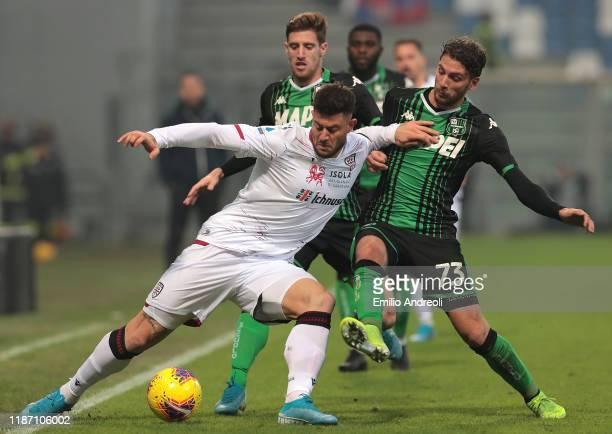 Alberto Cerri of Cagliari Calcio is challenged by Manuel Locatelli of US Sassuolo during the Serie A match between US Sassuolo and Cagliari Calcio at...