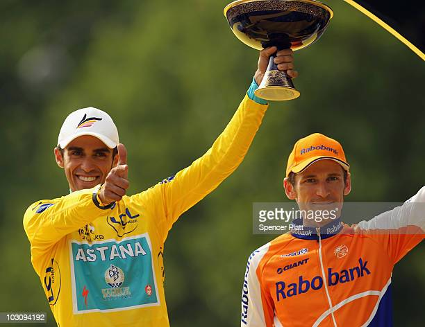 Alberto Contador of team Astana celebrates as Denis Menchov of team Rabobank looks on after the twentieth and final stage of Le Tour de France 2010,...