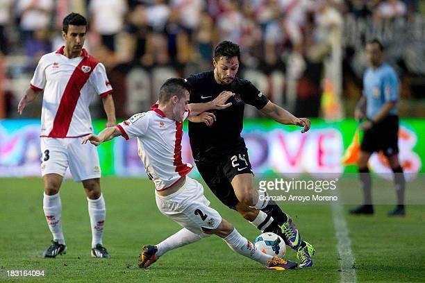 Alberto De la Bella of Real Sociedad competes for the ball with Roberto Roman alias Tito of Rayo Vallecano de Madrid during the La Liga match between...