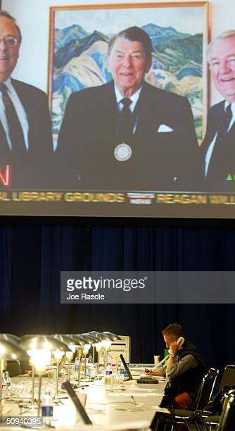 Alberto Gentili a reporter from Il Mesaggero sits under a large screen showing reports of former president Ronald Reagan's death at the G8 Summits...