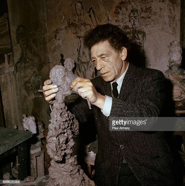 Alberto Giacometti at work on a sculpture of a human figure