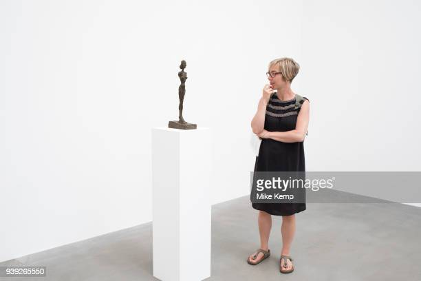 Alberto Giacometti exhibition at the Gagosian Gallery in London England United Kingdom People interacting with the sculptures within this white art...