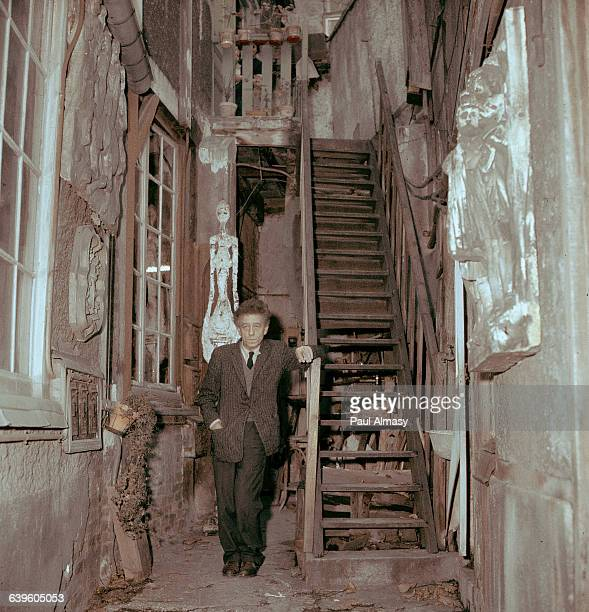 Alberto Giacometti stands in the alley between two buildings where the walls are decorated with his sculpture