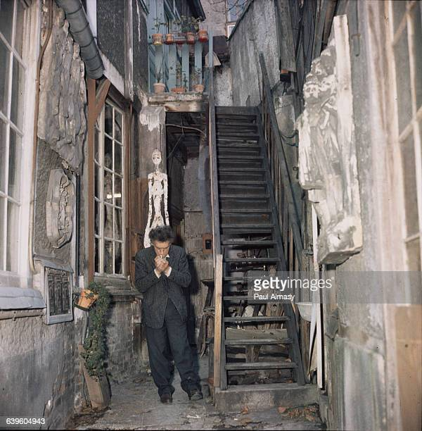 Alberto Giacometti stands in the stairwell to his house where the walls are decorated with his sculpture France 1958