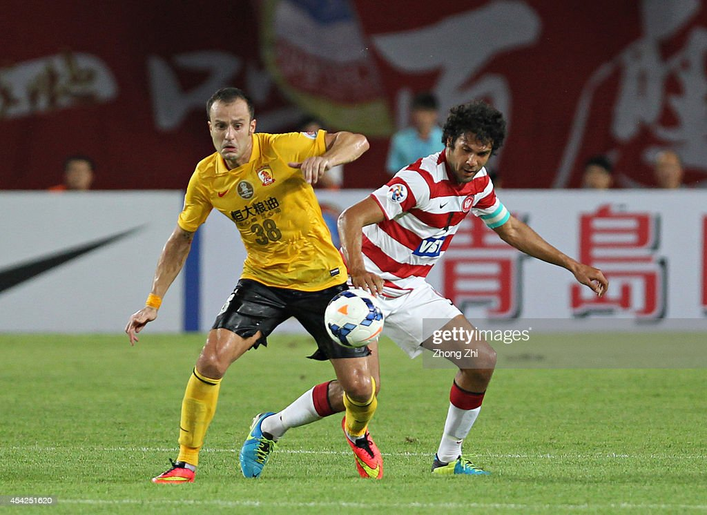 Alberto Gilardino of Guangzhou Evergrande competes the ball with Nikolai Topor-Stanley of Western Sydney Wanderers during the Asian Champions League Quarter Final match between the Western Sydney Wanderers and Guangzhou Evergrande at Tianhe Sports Center on August 27, 2014 in Guangzhou, China.