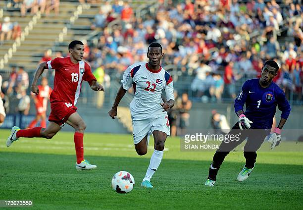 Alberto Gomez of Cuba races against goalkeeper Woodrow West and Dalton Eiley of Belize during their 2013 CONCACAF Gold Cup match July 16 2013 at...