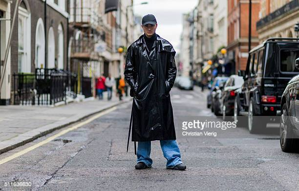 Alberto Grossule wearing a long black latex coat denim jeans and a cap seen during London Fashion Week Autumn/Winter 2016/17 on February 21 2016 in...