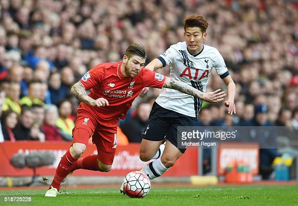 Alberto Moreno of Liverpool and Son Heungmin of Tottenham Hotspur compete for the ball during the Barclays Premier League match between Liverpool and...