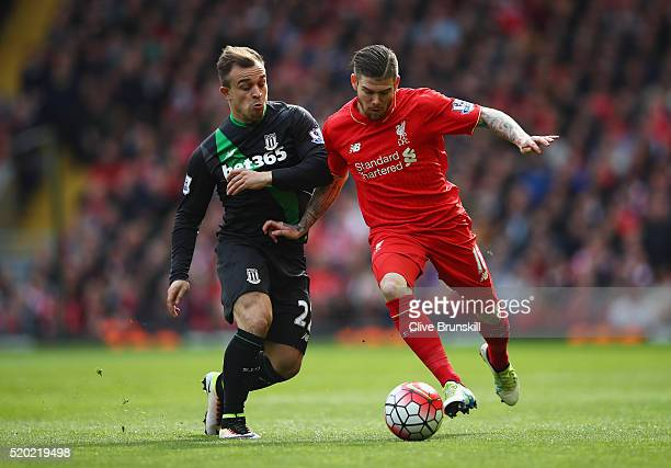 Alberto Moreno of Liverpool is challenged by Xherdan Shaqiri of Stoke City during the Barclays Premier League match between Liverpool and Stoke City...