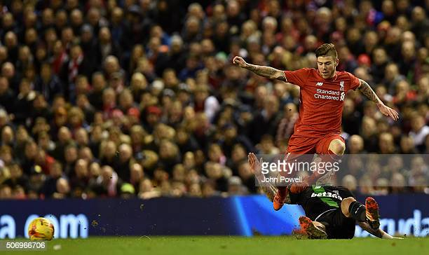 Alberto Moreno of Liverpool leaps over the challenge of Glenn Whelan of Stoke City during the Capital One Cup Semi Final Second Leg between Liverpool...