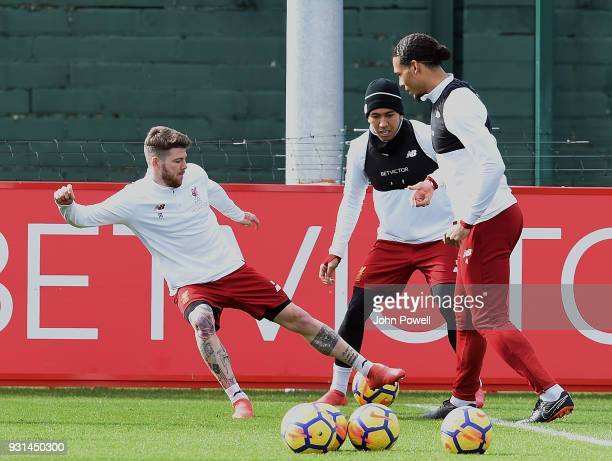 MARCH 13 Alberto Moreno with Virgil van Dijk and Roberto Firmino of Liverpool during a training session at Melwood Training Ground on March 13 2018...