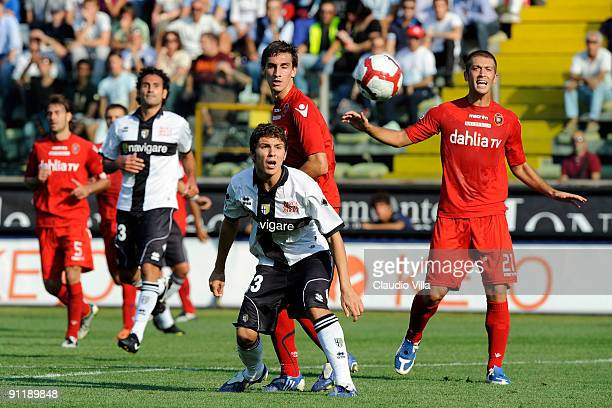 Alberto Paloschi of Parma FC competes for the ball with Michele Canini and Davide Astori of Cagliari Calcio during the Serie A match between Parma FC...
