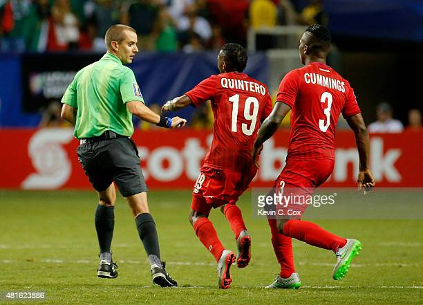 Alberto Quintero and Harold Cummings of Panama chase after referee Mark Geiger of the United States of America after their 21 loss to Mexico during...