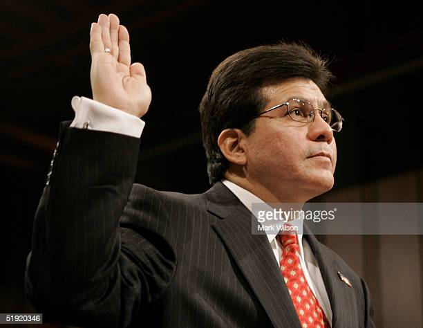 Alberto R Gonzales raises his right hand as he is sworn in during his Judiciary Committee confirmation hearing January 6 2005 in Washington DC US...