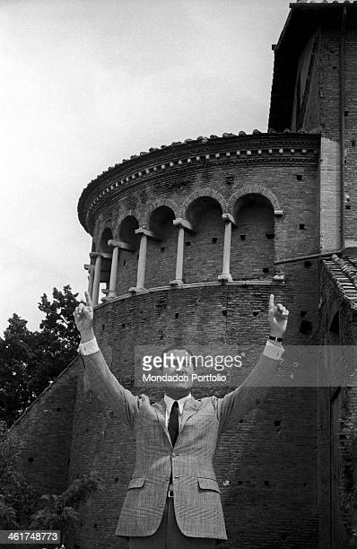 Alberto Sordi photographed on the terrace of his house as he rises his both hands the index fingers pointing up to show the hanging arches of a...
