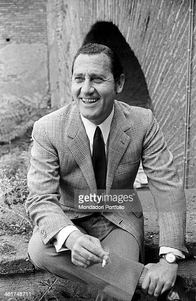 Alberto Sordi sits on an outer low wall of his house on the Caelian Hill smoking a cigarette and smiling during an interview the Italian movie star...