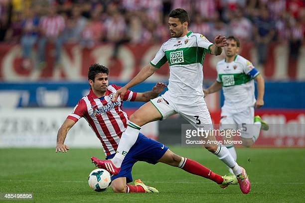 Alberto Tomas Botia of Elche FC tackles Diego Costa of Atletico de Madrid during the La Liga match between Club Atletico de Madrid and Elche FC at...