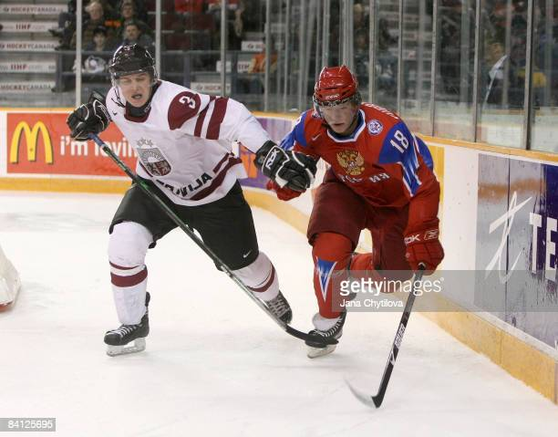 Alberts Ilisko of Latvia battles for the puck with Dmitri Kugryshev of Russia at the Civic Centre on December 26, 2008 in Ottawa, Ontario, Canada.