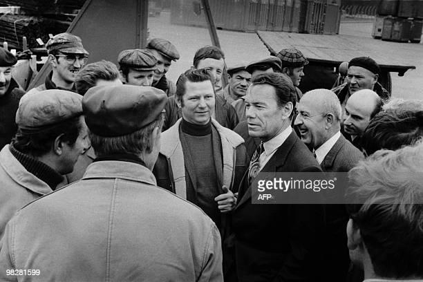 Albin Chalandon Ministre de l'Équipement et du Logement discute avec des dockers et visite les installatoins du port de Dunkerque le 20 avril 1971