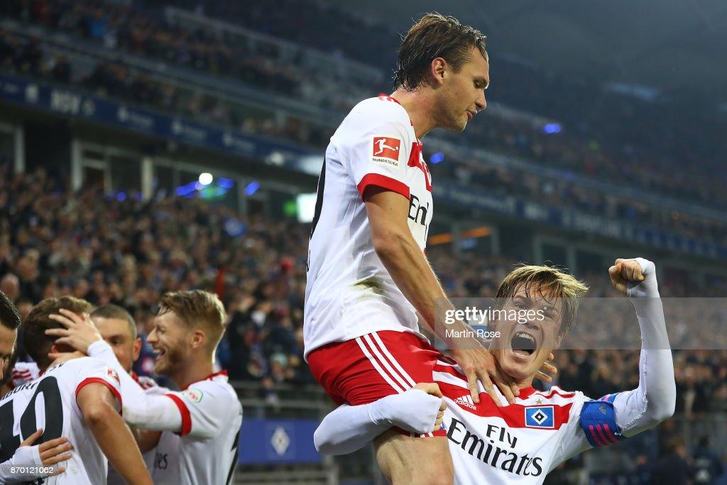 Albin Ekdal of Hamburg (top) celebrates with Gotoku Sakaiof Hamburg after Jann-Fiete Arp of Hamburg (covered) scored a goal to make it 3:1 during the Bundesliga match between Hamburger SV and VfB Stuttgart at Volksparkstadion on November 4, 2017 in Hamburg, Germany.