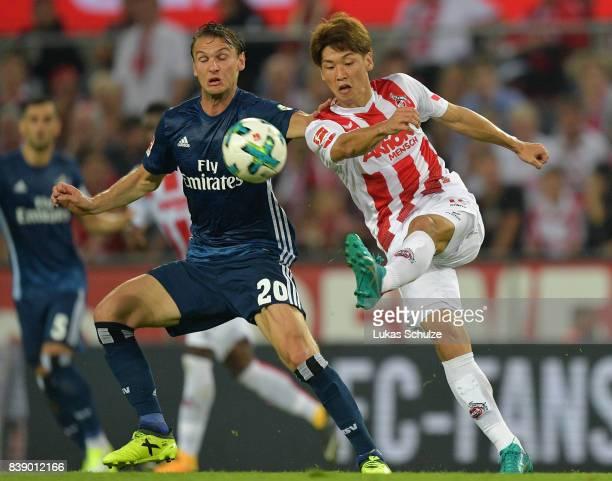 Albin Ekdal of Hamburg fights for the ball with Yuya Osako of Koeln during the Bundesliga match between 1 FC Koeln and Hamburger SV at...