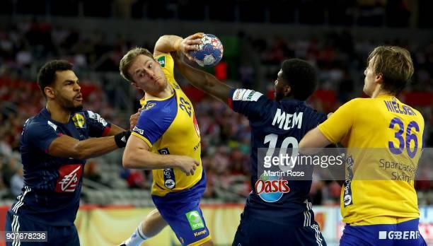 Albin Lagergren of Sweden challenges Dika Meme of France during the Men's Handball European Championship main round match between Sweden and France...