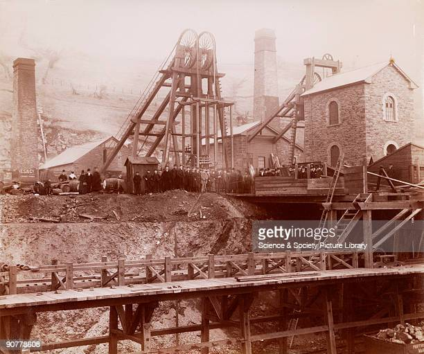 Albumen photographic print showing the pit head winding gear and coal trucks of a colliery at Ponsy Pool Miners can be seen assembled around the pit...