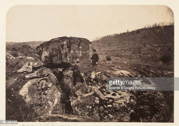 Albumen print of two doctors surveying dead bodies from both the Confederate and Union armies on the battlefield at Gettysburg, Pennysylvania. Little...