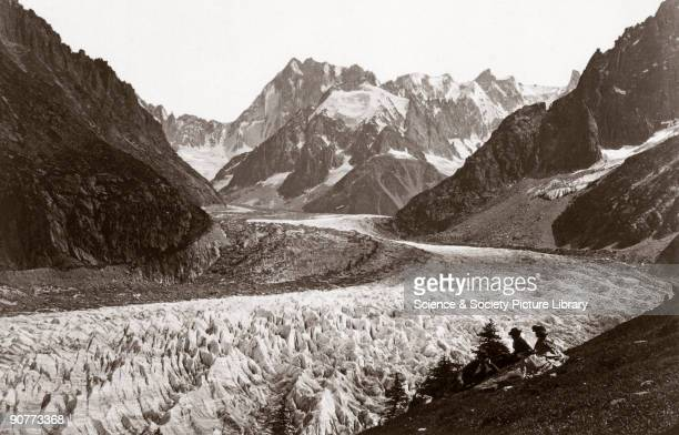 Albumen print showing two women and a man resting during a walk alongside the Mer de Glace near Chamonix with the summit of the Grandes Jorasses in...