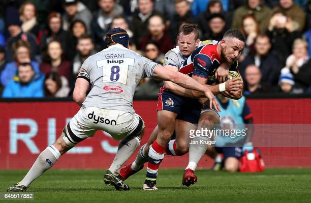Alby Mathewson of Bristol Rugby is tackled by Chris Cook and Paul Grant of Bath Rugby during the Aviva Premiership match between Bristol Rugby and...