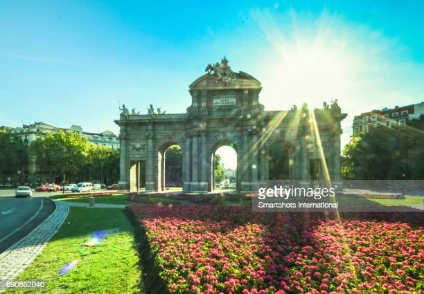alcala gate backlit with lens flare on a late afternoon before sunset in madrid, spain - porta cittadina foto e immagini stock