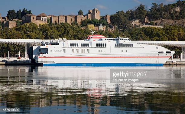 Alcantara Dos catamaran ferry at the quayside in new port development in Malaga Spain with the historic Alcazaba fortress behind