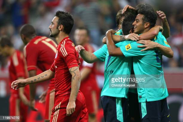 Alcantara Thiago of Barcelona celebrates the first goal with his team mates and Diego Contento of Bayern looks dejected during the Audi Cup final...
