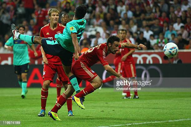Alcantara Thiago of Barcelona scores the first goal against Diego Contento of Bayernduring the Audi Cup final match between FC Bayern Muenchen and FC...