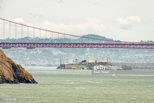 alcatraz under the golden gate bridge - alcatraz island stock pictures, royalty-free photos & images
