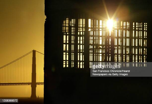 ALCATRAZ_0662_fljpg The setting sun beams through a maze of prison bars on the west end of the island with the Golden Gate Bridge in the background A...