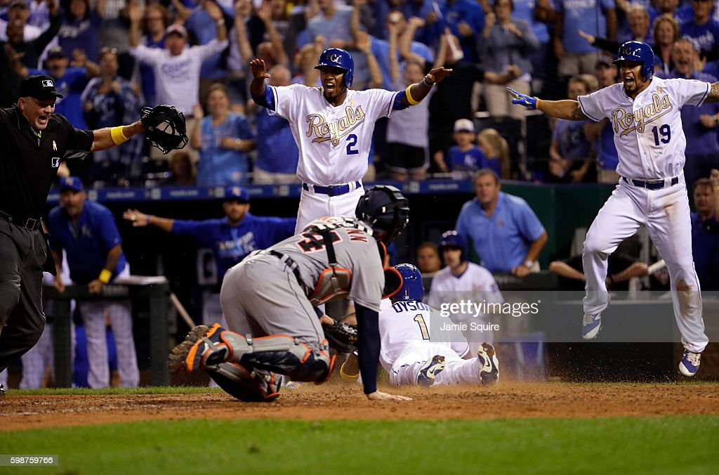 Alcides Escobar #2 and Cheslor Cuthbert #19 of the Kansas City Royals celebrate as Jarrod Dyson #1 slides safely into home plate to score during the 9th inning of the game against the Detroit Tigers at Kauffman Stadium on September 2, 2016 in Kansas City, Missouri.