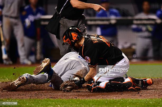 Alcides Escobar gets tagged out by Nick Hundley of the Baltimore Orioles on a grounded ball hit by Eric Hosmer of the Kansas City Royals to first...