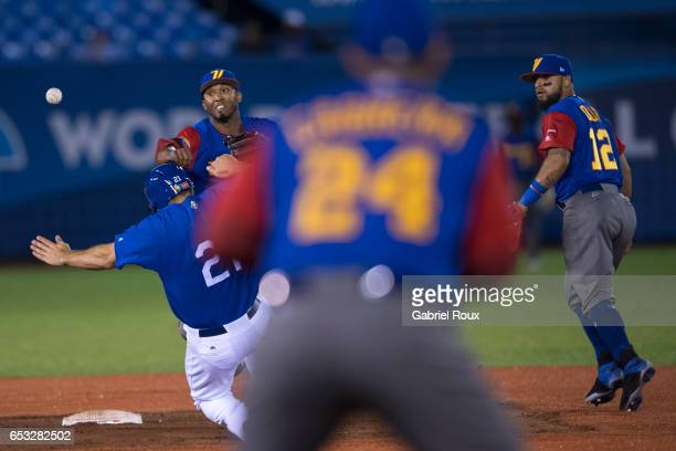 Alcides Escobar of Team Venezuela turns a double play as Rob Segedin of Team Italy slides into second base during Game 6 of Pool D of the 2017 World...