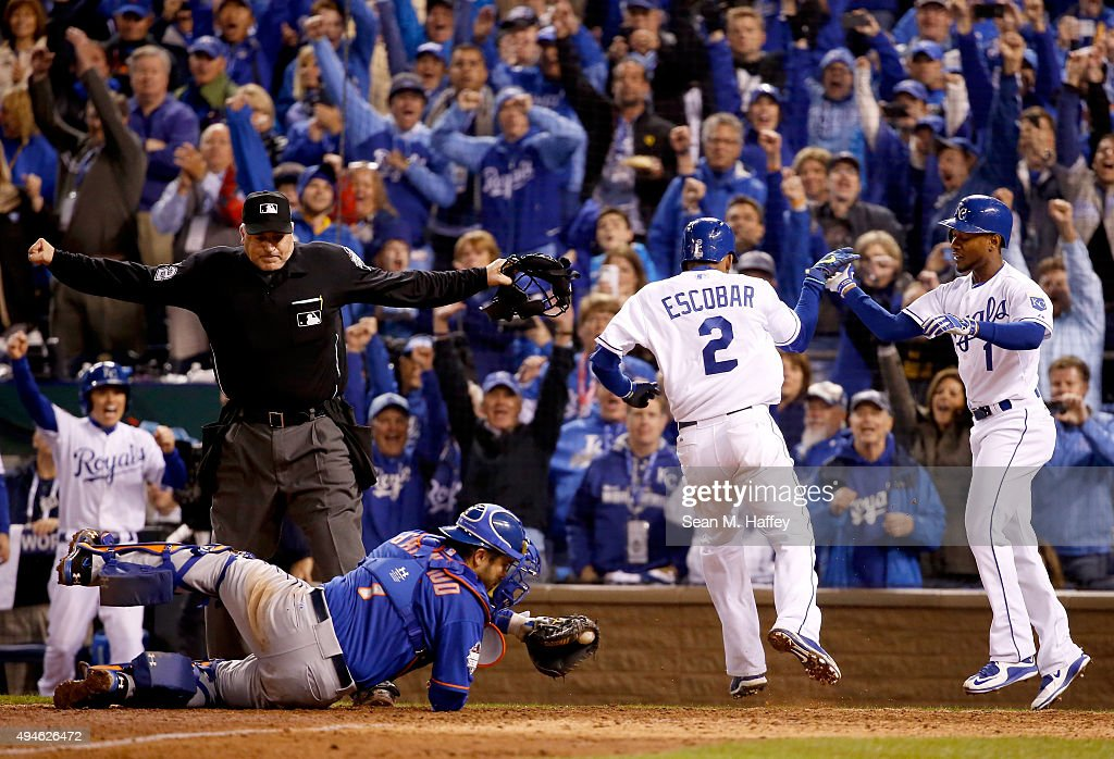 Alcides Escobar #2 of the Kansas City Royals celebrates with Jarrod Dyson #1 of the Kansas City Royals after scoring the game-winning run in the fourteenth inning against the New York Mets during Game One of the 2015 World Series at Kauffman Stadium on October 27, 2015 in Kansas City, Missouri. The Kansas City Royals defeat the New York Mets with a score of 5 to 4 in fourteen innings.
