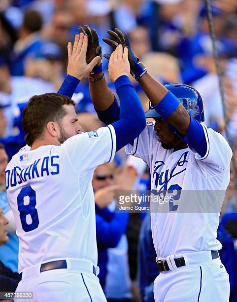 Alcides Escobar of the Kansas City Royals celebrates with Mike Moustakas after scoing on Eric Hosmer of the Kansas City Royals grounder into...